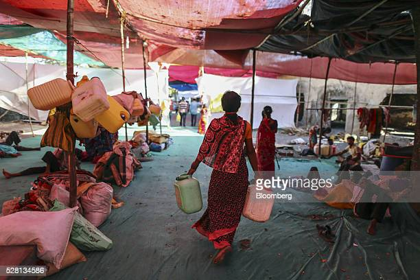 A woman carries empty water cans inside a temporary suburban camp set up by local political party Shiv Sena for the rural poor traveling to Mumbai to...