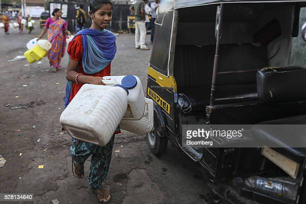 Woman carries empty water cans past an auto-rickshaw outside Mumbra railway station in Mumbai, India, on Sunday, April 17, 2016. Hundreds of millions...