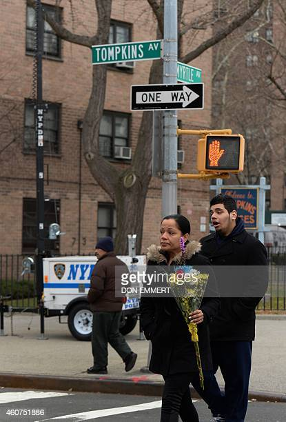 A woman carries flowers accross Tompkins Ave on her way to place flowers at the site where two New York City police officers were shot and killed...