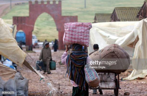A woman carries goods at the Dar Chaffai Market April 18 2004 in Bni Meskine central Morocco about an hour inland by car from Casablanca Inhabitants...