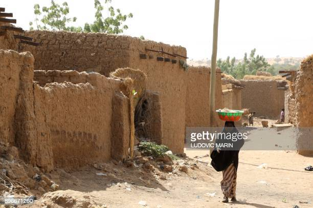 A woman carries goods while walking down a street in Niamey on December 21 2017 / AFP PHOTO / LUDOVIC MARIN