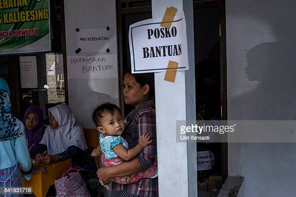 A woman carries her baby at the temporary shelter after a landslide on June 21 2016 in Purworejo Indonesia At least 47 people were killed in...