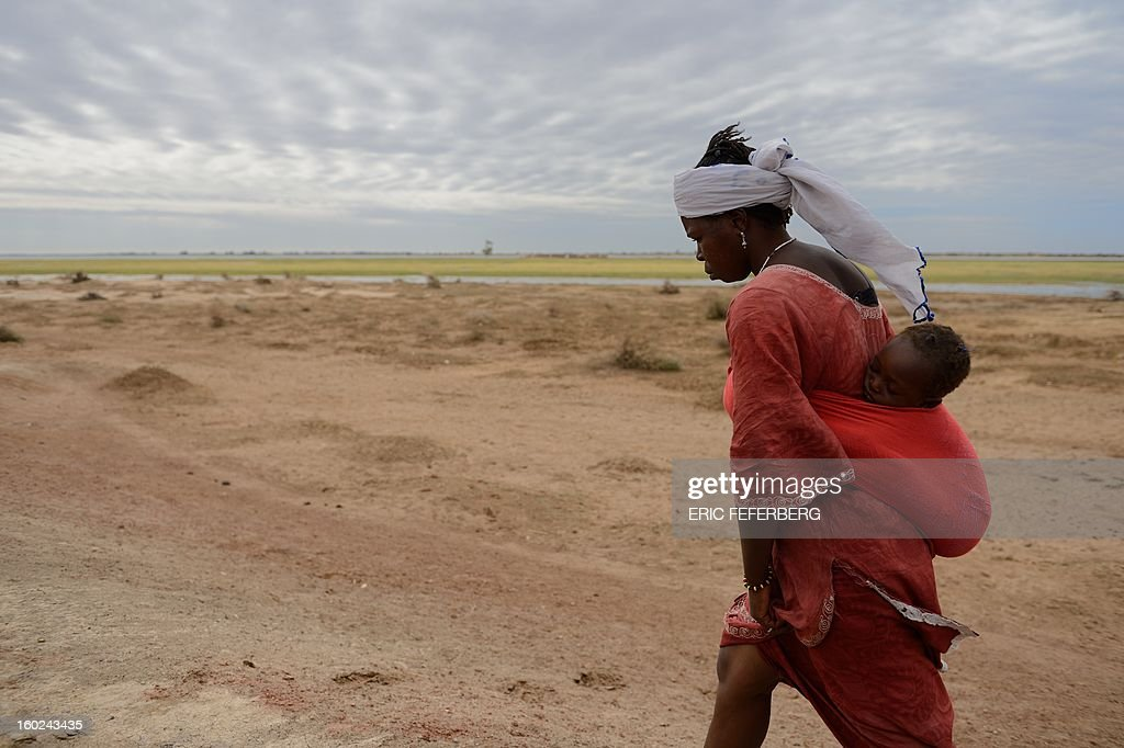 A woman carries her baby in Niafounke after Malian and French soldiers entered the historic city of Timbuktu, occupied for 10 months by Islamists who imposed a harsh form of sharia, on January 28, 2013. French-led forces today seized Mali's fabled desert city of Timbuktu in a lightning advance north as fleeing Islamists torched a building housing priceless ancient manuscripts. Residents of the ancient city on the edge of the Sahara desert erupted in joy as the French-led troops entered the town, jubilantly waving French and Malian flags after months of suffering under the Islamists' brutal rule.