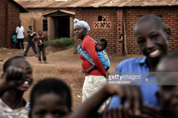 A woman carries her baby in the outskirts of Lilongwe on March 11 2016 / AFP / ARIS MESSINIS / RESTRICTED TO EDITORIAL USE
