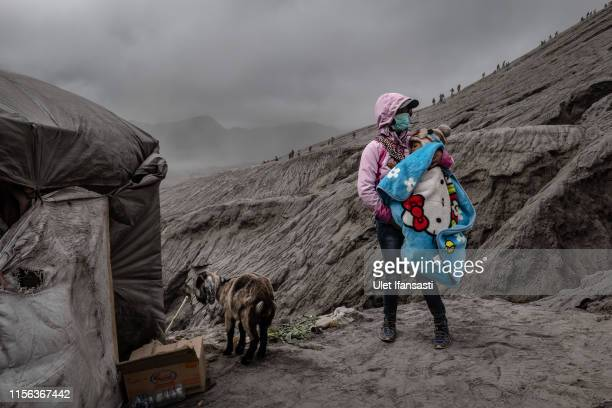 A woman carries her baby near a goat result of catch thrown by Tenggerese worshippers during the Yadnya Kasada Festival at crater of Mount Bromo on...