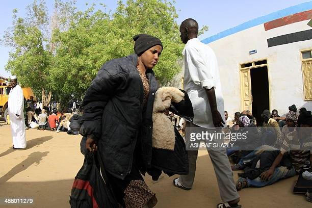 A woman carries her bag as illegal migrants who were abandoned in the desert by human traffickers arrive at a military building in the northern...