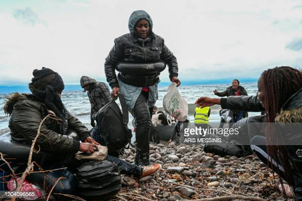Woman carries her belongings as a dinghy transporting 27 refugees and migrants originating from Gambia and the Republic of Congo lands in Lesbos...