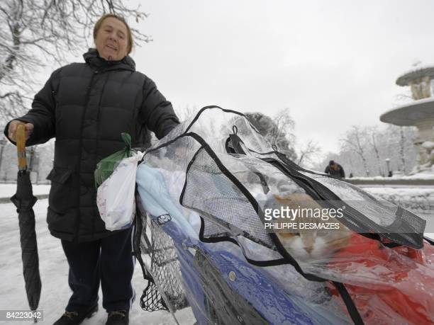 A woman carries her cat in a pushchair covered by plastic in a street of Madrid on January 9 2009 Heavy snowfall disrupted road transportation on...