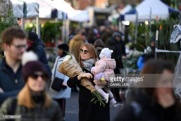 A woman carries her child and a bunch of flowers during a visit to Columbia Road flower market in east London on Mother's Day March 22 2020 Up to 15...