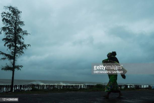 A woman carries her child as she walks along a road near the Tajpur Beach to take shelter ahead of the expected landfall of cyclone Amphan in...