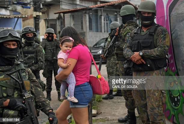 A woman carries her child as she walks past military police on patrol near the Vila Kennedy favela in Rio de Janeiro on February 23 2018 More than...