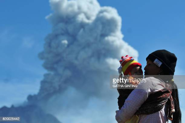 TOPSHOT A woman carries her child as she watches Mount Sinabung volcano spewing thick volcanic ash as seen from Karo on July 21 2017 Sinabung roared...