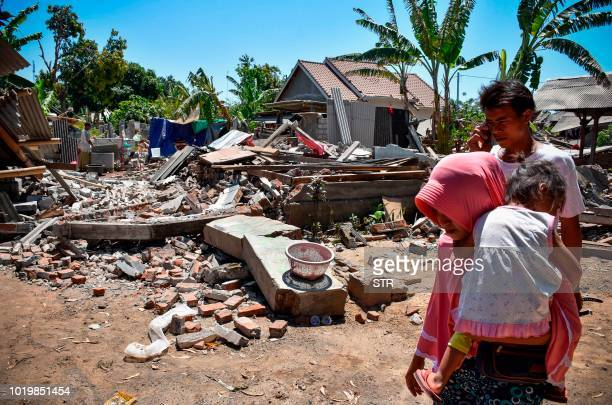 TOPSHOT A woman carries her child as they make their way pass collapsed homes in the village of Sugar on Indonesia's Lombok island on August 20 2018...