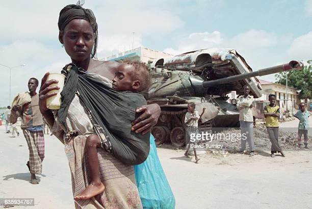 Woman carries her child in an area that divides the city into north and south sections. It is a no-man's-land where homes and businesses have been...