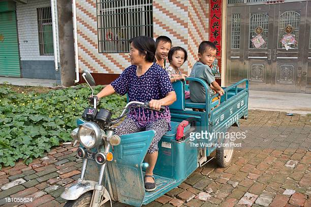 A woman carries her grand children in a motor rickshaw in a rural village near Fuyang Anhui Province China on 28 August 2013 As ablebodied adults...