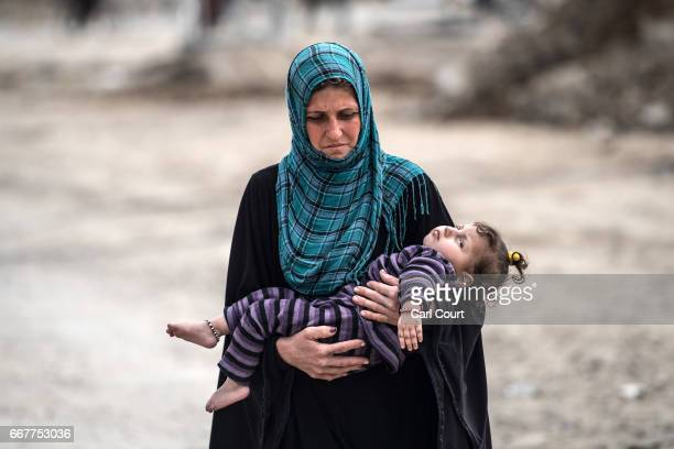 Woman carries her niece who is suffering from an undiagnosed disease and cannot walk or talk, as she makes her way to a food distribution point as...