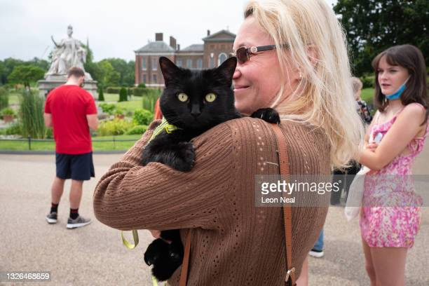 Woman carries her pet cat, Mitty, as people gather on what would have been the 60th birthday of Princess Diana, at Kensington Palace on July 01, 2021...