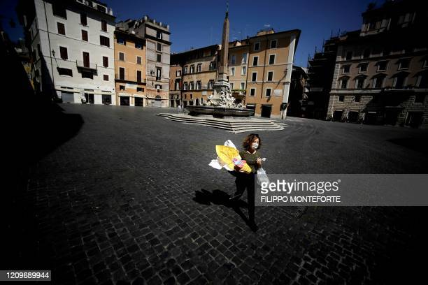 TOPSHOT A woman carries her shopping and an Easter egg across Piazza della Rotonda in central Rome on April 11 2020 during the country's lockdown...