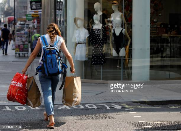 Woman carries her shopping in bags as she walks past a clothes shop in London on August 12, 2020. - Britain's economy contracted by a record 20.4...