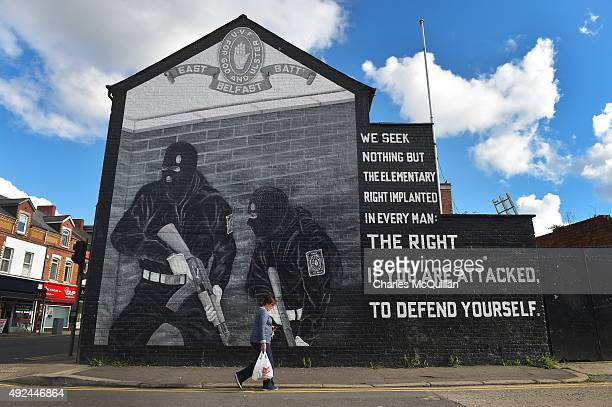 A woman carries her shopping past a loyalist paramilitary mural on the day that the new Loyalist Community Council was launched at the Park Avenue...
