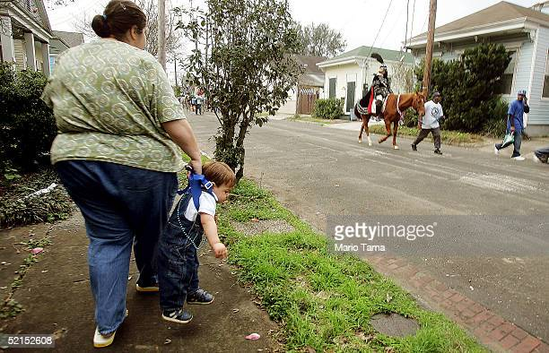 A woman carries her son as a mounted horseman passes during the historic Proteus parade founded in 1882 during Mardi Gras festivites February 7 2005...
