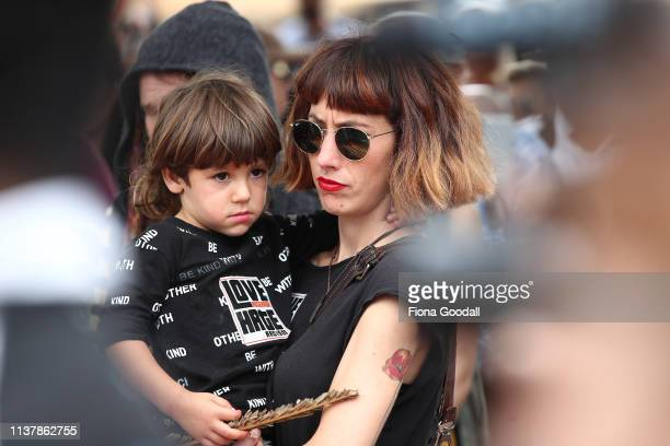 A woman carries her son during a march against racism at Aotea Square on March 24 2019 in Auckland New Zealand 50 people were killed and dozens were...