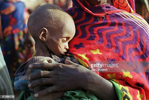 Woman carries her starving child 09 April 2000 in the Danan aera, 75 kilometers from the Ethiopian city of Gode. Some 26,000 persons gathered in the...