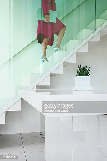 woman carries laptop up stairs in a modern office