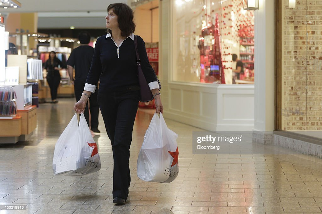 A woman carries Macy's Inc. shopping bags while walking through the Fair Oaks Mall in Fairfax, Virginia, U.S., on Monday, Nov. 12. 2012. Sales at U.S. retailers probably fell in October for the first time in four months economists said before a report on Nov. 14. Photographer: Andrew Harrer/Bloomberg via Getty Images