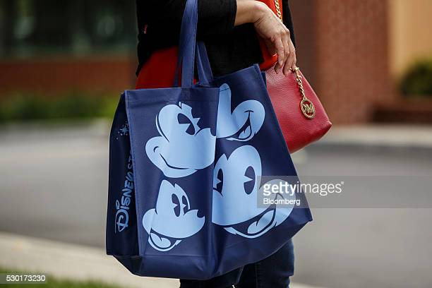 A woman carries Mickey Mouse bag while walking outside of The Walt Disney Co Studios in Burbank California US on Monday May 9 2016 The Walt Disney Co...