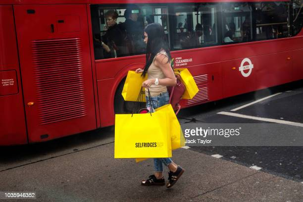 A woman carries Selfridges shopping bags as she crosses Oxford Street on September 19 2018 in London England UK inflation increased from 25% in July...