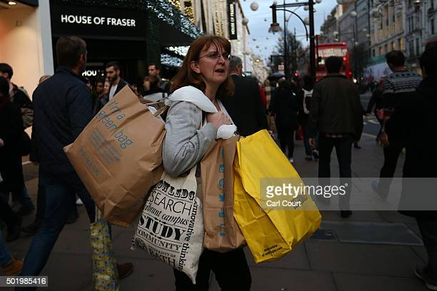 A woman carries several shopping bags as she shops on Oxford Street on December 19 2015 in London England Shoppers have taken to the high street on...
