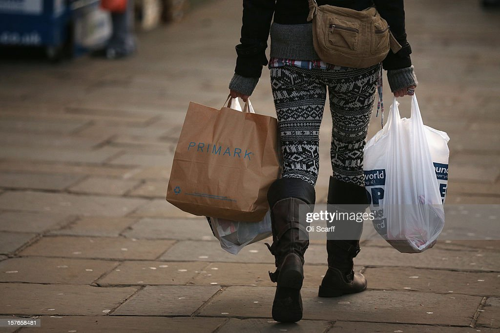 A woman carries several shopping bags from discount shops along Lewisham high street on December 5, 2012 in London, England. The Chancellor of the Exchequer George Osborne has stated that the United Kingdom's economy is still struggling during his autumn budget statement to Parliament.