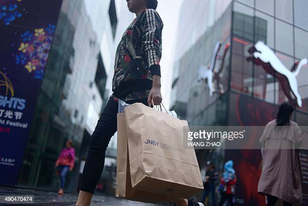 A woman carries shopping bags as she walks past a mall in Beijing on September 29 2015 Growth in China's industrial production and retail sales...
