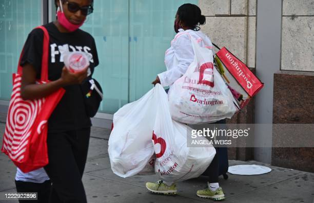 Woman carries shopping bags from Burlington department store near Union Square on June 25, 2020 in New York City. - New York businesses opened their...