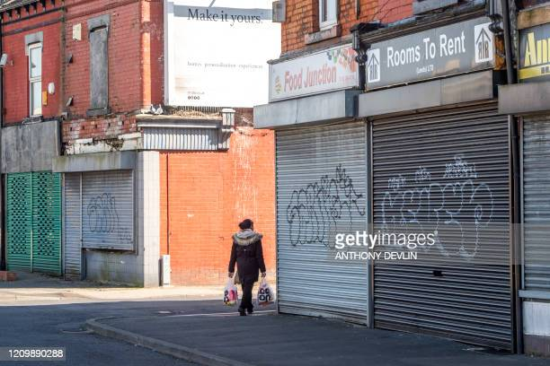 A woman carries shopping past closed shops in Leeds city centre West Yorkshire on April 14 as life in Britain continues during the nationwide...