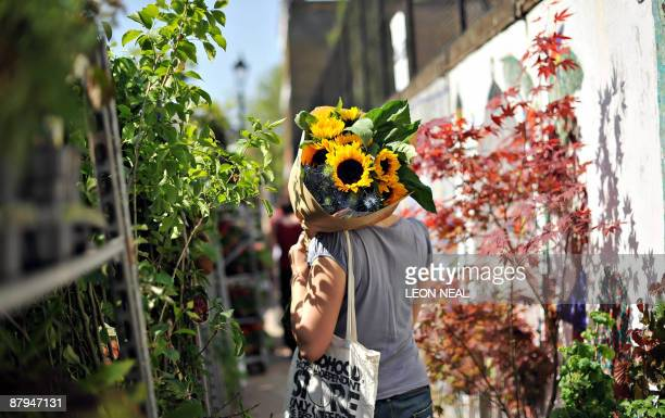 A woman carries sunfloweres at the Columbia Road flower market in East London as summer weather hit the United Kingdom on May 24 2009 AFP PHOTO/Leon...