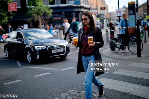 Woman carries takeaway draught beer in plastic cups from a pub in Broadway Market, London on June 5 as lockdown measures are eased during the novel...