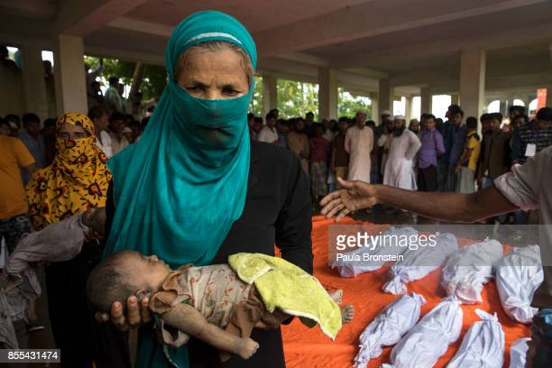 A woman carries the body of a child to be washed in preparation for the funeral after a boat sunk in rough seas off the coast of Bangladesh carrying...