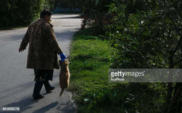 A woman carries the body of her dog which was killed by the blast debris following an explosion at an ammunition depot in Kalynivka city not far from...