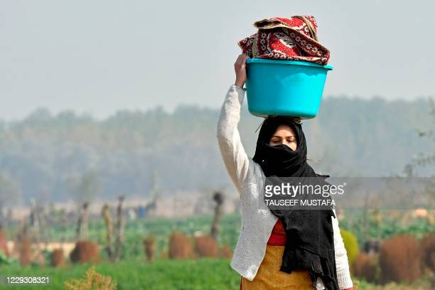 Woman carries the lunch for her relatives at a vegetable field on the outskirts of Srinagar on October 27, 2020.