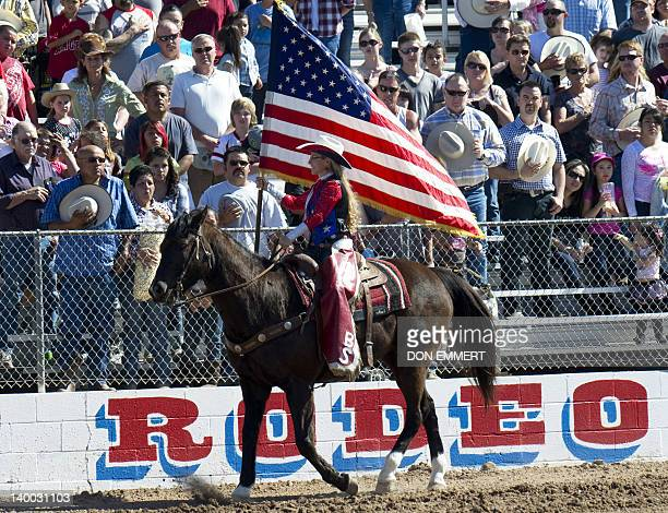 A woman carries the US flag on horse back at the Tucson Rodeo La Fiesta De Los Vaqueros February 26 2012 in Tucson Arizona AFP PHOTO/DON EMMERT