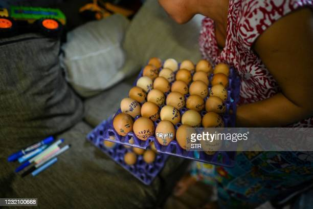 Woman carries trays of eggs, with messages in support of protesters demonstrating against the military coup, which will be given out to customers in...