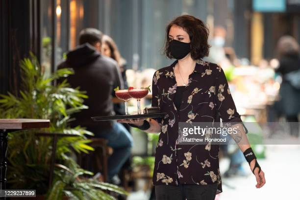 Woman carries two cocktails on a tray while wearing a face mask at a bar on St. Mary Street on October 23, 2020 in Cardiff, Wales. Wales will go into...