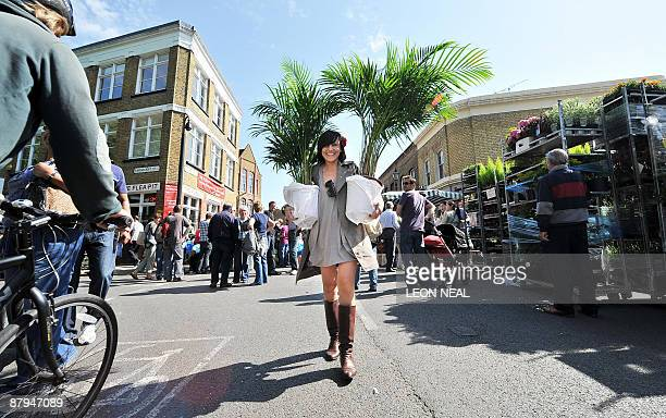 A woman carries two large plants away from the Columbia Road flower market in East London as summer weather hit the United Kingdom on May 24 2009 AFP...