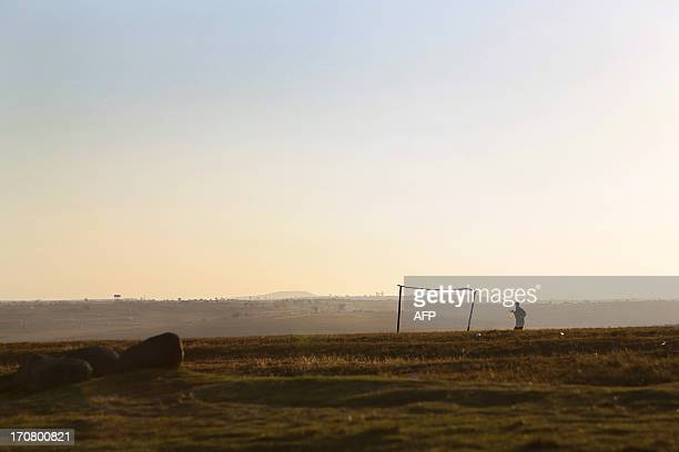 A woman carries water across a makeshift football field on June 13 2013 in Qunu a village outside the town of Mthatha in the Eastern Cape where...