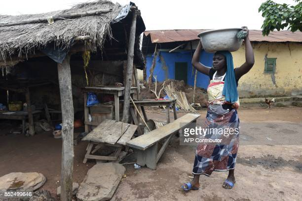 A woman carries water following alleged incessant harassment by the military at Kparatao village near Tchamba in the northern region of Togo the home...