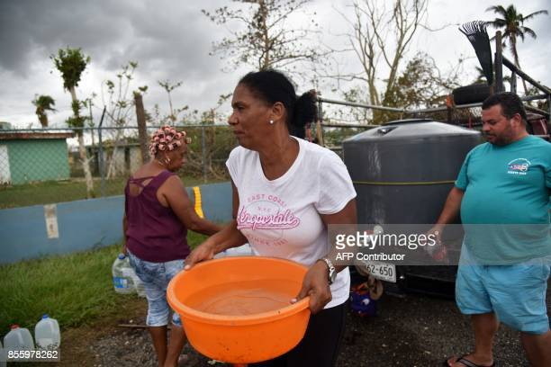 A woman carries water taken from a tank in Vega Baja Puerto Rico on September 30 due to the lack of water after the passage of Hurricane Maria US...