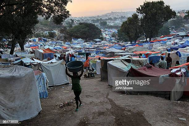 A woman carries water through the largest camp for earthquake refugees on February 6 2010 in PortauPrince Haiti More than 212000 people were believed...