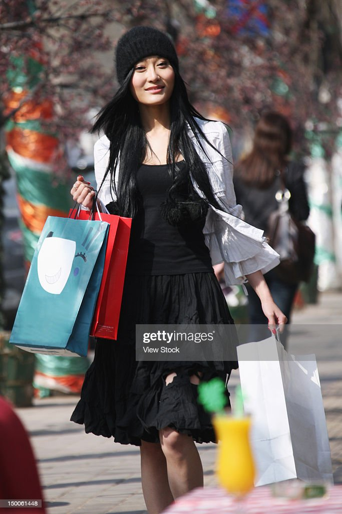 Woman carring shopping bags walking along street : Bildbanksbilder